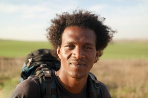 Portrait of cheerful african american young man with Hiking backpack. He looks at camera and smiling
