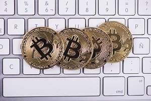 Bitcoin coins on computer keyboard. Cryptocurrency