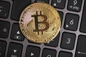 Bitcoin coin on laptop keyboard. Cryptocurrency