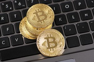 Bitcoin coins on laptop keyboard. Cryptocurrency