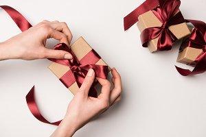 woman tying ribbon on gift box