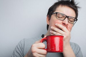 Sleepy yawning man in eyeglasses with red cup of tea or coffee has uncombed hair in underwear on light background, morning refreshment and drink. Copy space for your text