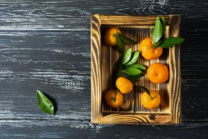 Tangerines on a wooden tray
