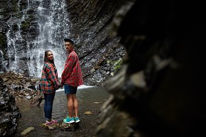 Couple holding hands on waterfall