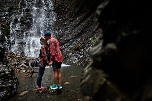 Couple kissing near waterfall