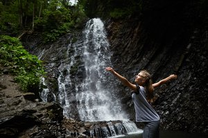 Blonde Woman dancing near waterfall