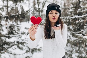 Woman holding red heart.