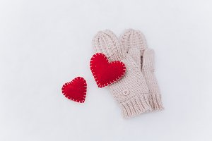 A mittens and red decorative hearts.