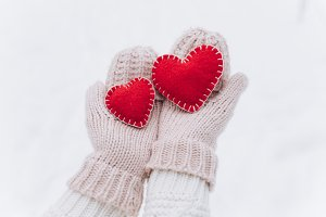Female hands holding red hearts.