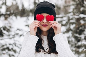 Girl holding two red hearts.