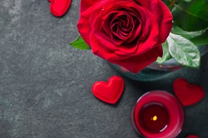 Valentines day greeting card concept. Red rose and candle on black background