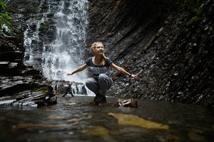 Girl in the river near the waterfall