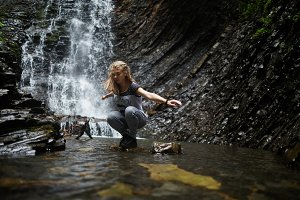 Blonde Woman sitting near waterfall
