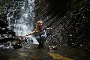 Woman sitting near waterfall