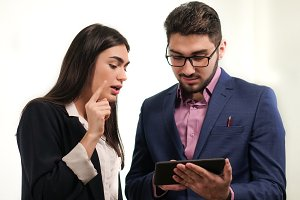 Portrait of business partners young man holding a tablet in hands and woman turned up her finger