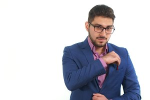 Young businessman with beard takes out a pen from his pocket in business suit on white background