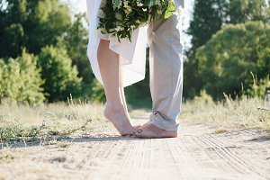 Happy newlyweds standing barefoot