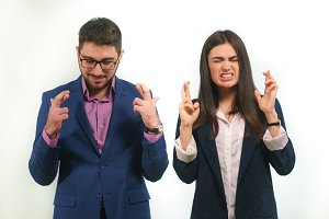 Guy and a girl in business suits crossed their fingers sincerely wishing for the successful project start