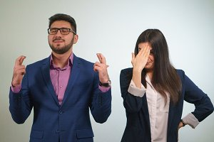 Business partner crossed their fingers the girl funny criticizes her colleague who has closed eyes happily raised his head in prayer