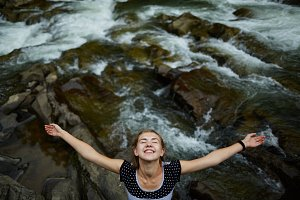 Woman hangs over the river smiling