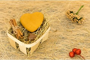 Cookies and chocolates in the form of heart. Basket with hay.
