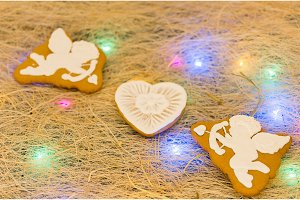 Gingerbread cookies in the form of cupids and hearts. Multicolored garland.