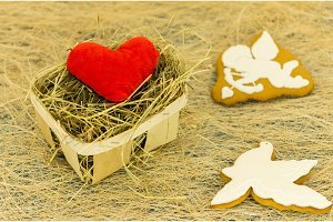 Red heart and ginger biscuits in the form of a cupid and a white dove. Wicker basket and cookies.
