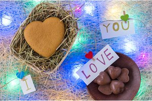 Gingerbread in heart shape in a wicker basket. Chocolate candies. I love you. Multicolored garland.