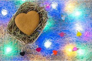 Gingerbread in heart shape in a wicker basket. Multicolored garland.