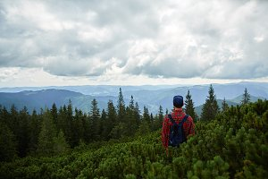 Man with a backpack hikes mountains