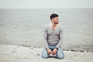 Handsome guy sitting on the sand