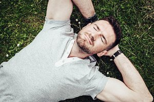 Happy guy lying on the green grass