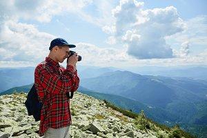 A man photographs a landscape
