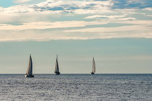 A fiew sailboats are traveling
