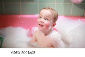 Two year old boy taking a bath