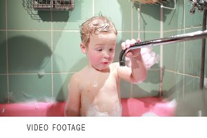 Two year old boy plays in the bath.