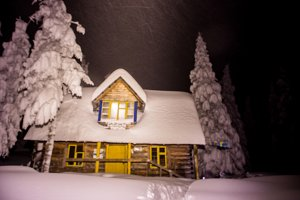 Tourist house in the winter mountains. Night in the forest.