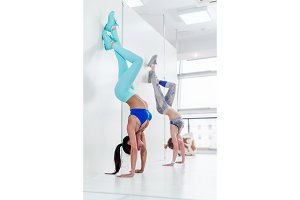 Young sporty women doing handstand exercise. Athletic girls standing in advanced downward-facing tree pose leaning against wall during yoga class indoors
