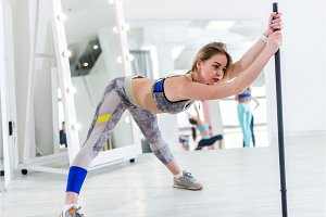 Woman doing stretching exercise for hamstrings and back leaning forward holding barbell in one hand