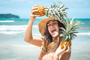 beautiful girl with pineapple on an exotic beach, a happy mood and a beautiful smile