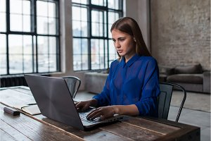 Pretty young brunette working on laptop at wooden table in spacious dark loft studio