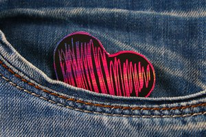 Heart - a symbol of love peeps out of the pocket of jeans trousers. The concept of the day of lovers. St. Valentine's Day.