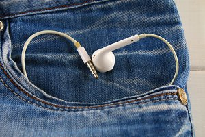 Heart of white headphones - a symbol of love peeps out of the pocket of jeans trousers. Love for music. The concept of the day of lovers. St. Valentine's Day.