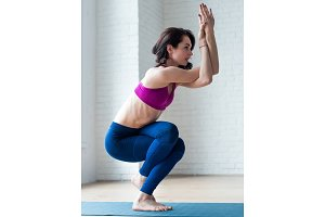 Slim young female in sportswear doing Eagle pose, Garudasana, in gym