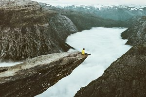 Man traveler on Trolltunga cliff