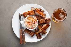 Grilled pork ribs in barbecue sauce and honey with sauerkraut and beer on a white plate. Snack to beer on a light stone table. Top view with copy space