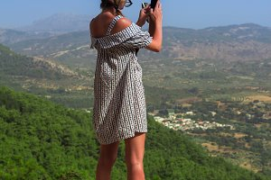 Caucasian woman in a dress photographing mountains