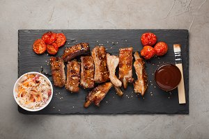 Grilled pork ribs in barbecue sauce and honey with sauerkraut and roasted tomatoes on a black stone Board. Snack to beer on a light stone background. Top view