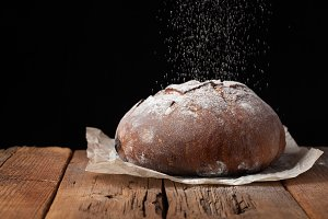 Tasty rustic bread on wooden table on black background with copy space for text. Dark bread sprinkled with white flour
