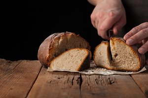 Man slices of delicious fresh bread on black background with copy space for your text. The loaf on the old rustic table